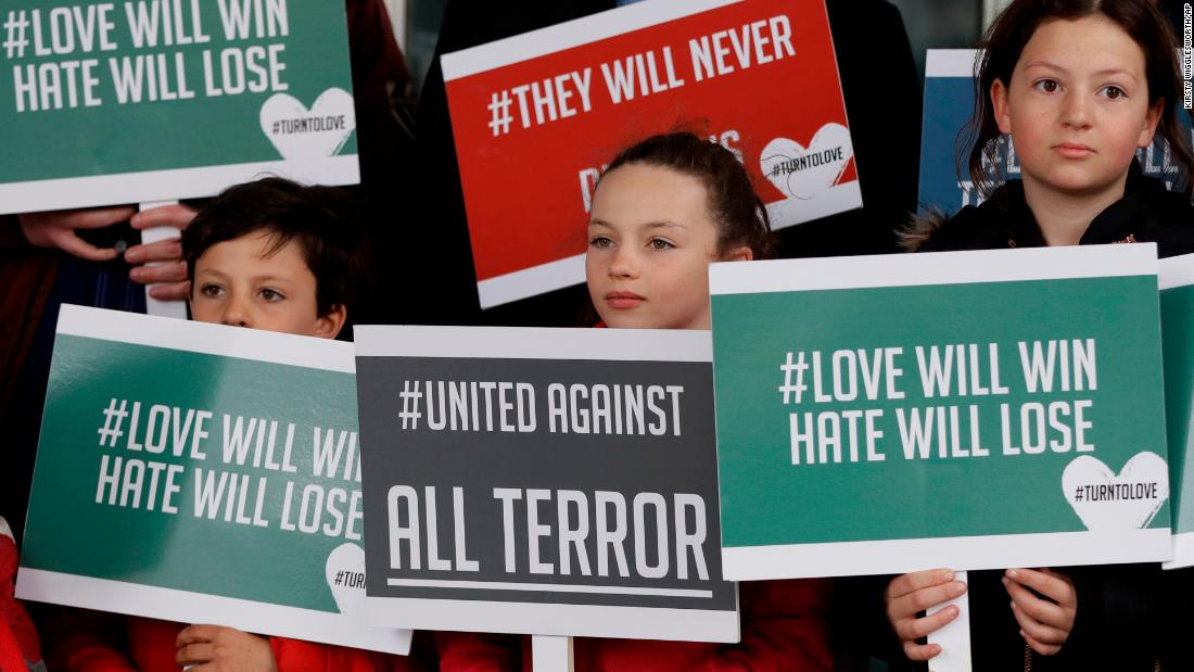 Young demonstrators hold banners from the multifaith group Turn to Love during a vigil at the New Zealand House in London.