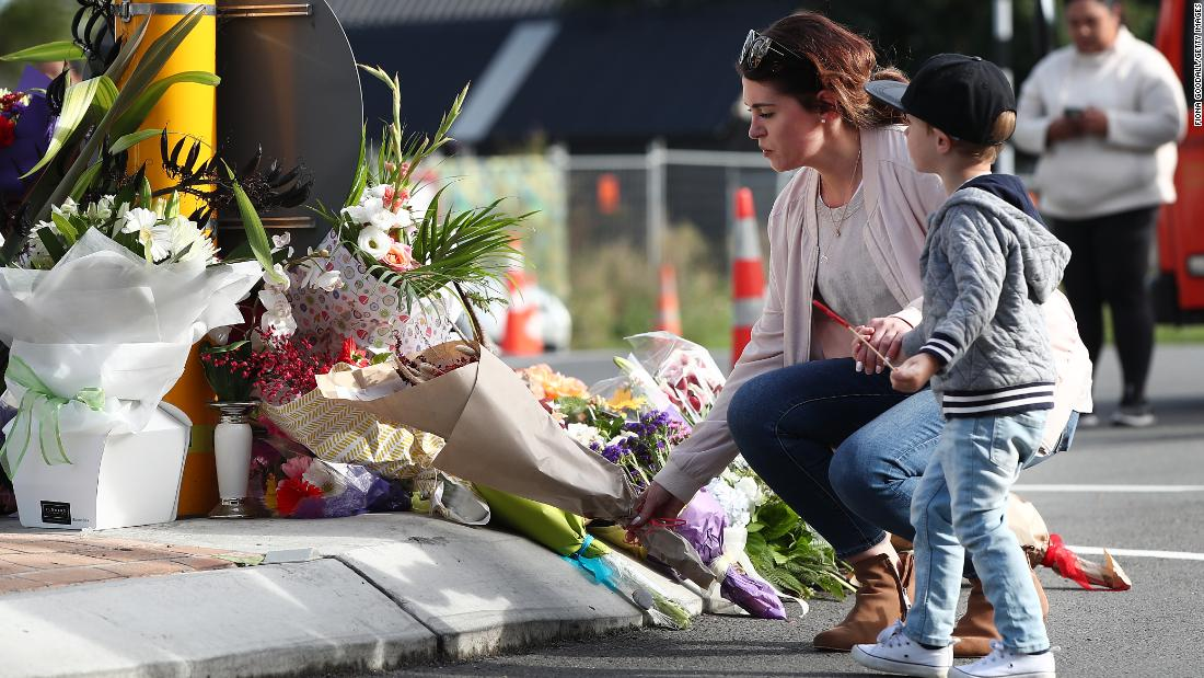 A woman lays flowers at Deans Avenue near Al Noor Mosque in Christchurch on March 16. More than 40 people were killed at that mosque, according to authorities
