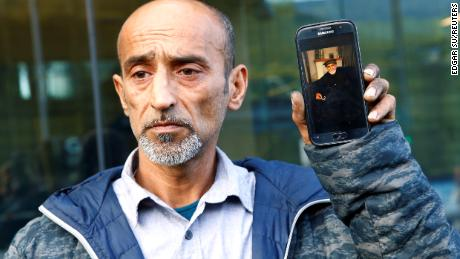 Omar Nabi raccroche un téléphone affichant une photo de son père décédé, Haji Daoud, au tribunal de district de Christchurch.