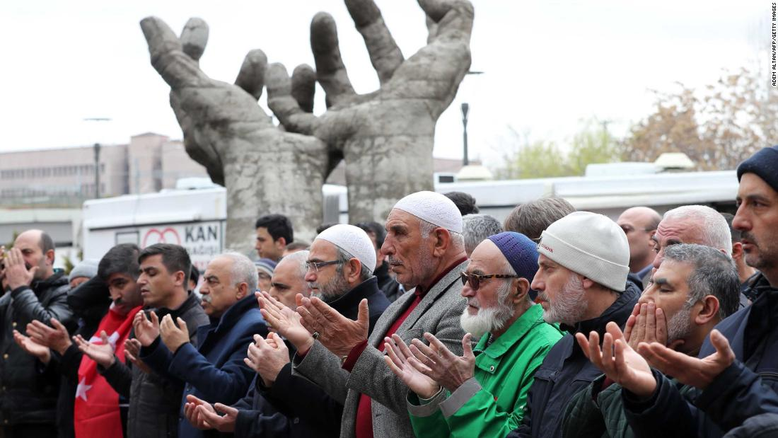 People perform a funeral prayer in absentia on March 16 in Ankara, Turkey.