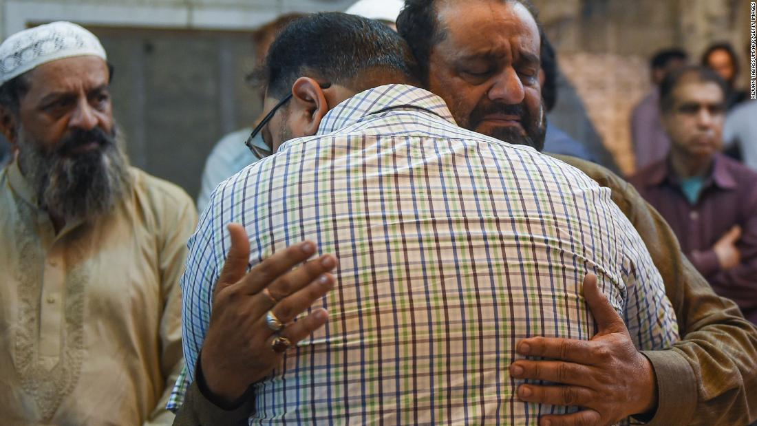 A Pakistani man embraces the father of Syed Areeb Ahmed (right), reportedly gunned down in the New Zealand massacre, in Karachi on March 16.