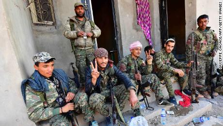 """Fighters from the Syrian Democratic Forces returning from the frontline in Baghouz flash the """"V"""" for victory sign."""