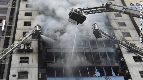 Bangladeshi firefighters on ladders work to extinguish a blaze in an office building in Dhaka on March 28, 2019. - A huge fire tore through a Dhaka office block March 28 killing at least five people with many others feared trapped in the latest major inferno to hit the Bangladesh capital. (Photo by MUNIR UZ ZAMAN / AFP)        (Photo credit should read MUNIR UZ ZAMAN/AFP/Getty Images)