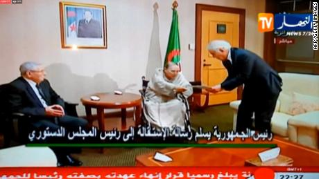 A TV grab from Ennahar TV shows Abdelaziz Bouteflika, center, hand in his resignation letter to the Constitutional Council in Algiers.