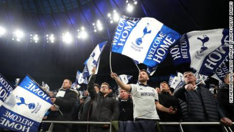 Spurs fans wave flags before the first Premier League game at the  new stadium.