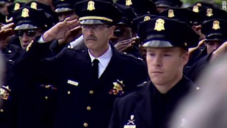 Fellow officers salute at the funeral of Isaac Espinoza, in April 2004.
