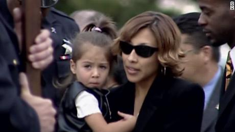 Renata Espinoza holds her daughter at her husband's funeral.