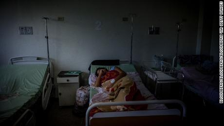 A patient lays on a bed inside the Ana Teresa de Jesus Ponce maternity hospital in Macuto, Venezuela, on Friday, Feb. 22, 2019. Venezuela's healthcare system, a shining example in Latin America back when the government had the money for ambitious programs, has been crumbling for many years: nearly half the country's doctors have left and hospital regularly go without the necessary equipment needed to fully function. Photographer: Adriana Loureiro Fernandez/Bloomberg via Getty Images