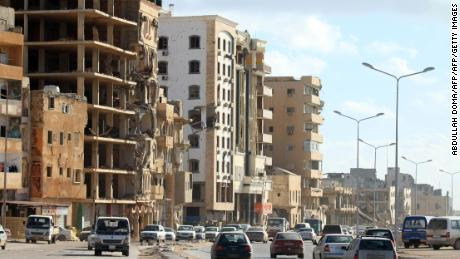 Cars drive past buildings, heavily damaged from previous clashes in Libya's eastern city of Benghazi on April 8, 2019.