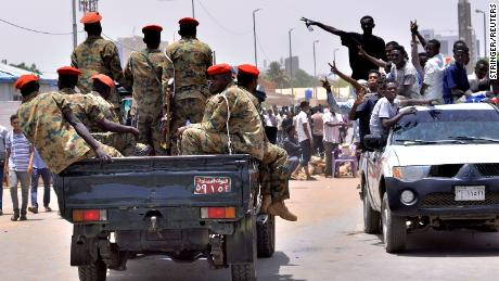 Sudanese demonstrators cheer as they drive towards a military vehicle.