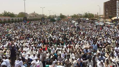 Sudanese protesters gather near the military headquarters in Khartoum as they continue to rally demanding a civilian body to lead the transition to democracy one day after a military council took control of the country, on April 12, 2019.