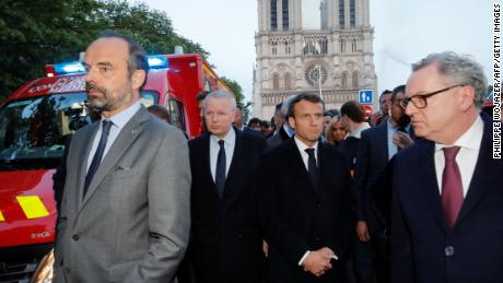 French Prime Minister Edouard Philippe (L), and French President Emmanuel Macron (3rd L) gather in near the entrance of the Notre-Dame de Paris Cathedral in Paris, as flames engulf its roof on April 15, 2019. - A huge fire swept through the roof of the famed Notre-Dame Cathedral in central Paris on April 15, 2019, sending flames and huge clouds of grey smoke billowing into the sky. The flames and smoke plumed from the spire and roof of the gothic cathedral, visited by millions of people a year. A spokesman for the cathedral told AFP that the wooden structure supporting the roof was being gutted by the blaze. (Photo by PHILIPPE WOJAZER / POOL / AFP)        (Photo credit should read PHILIPPE WOJAZER/AFP/Getty Images)