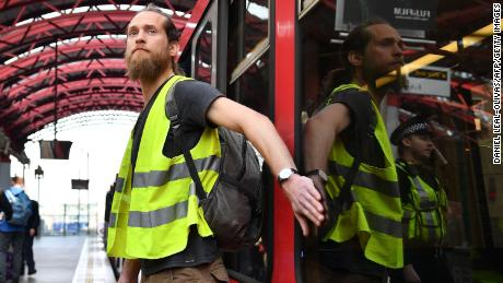 A climate change protestor who glued his hand to a window halts a train at Canary Wharf station on Wednesday.