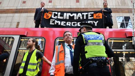 Police stand by as climate change protestors block a DLR train at Canary wharf station on the third day of an environmental protest by the Extinction Rebellion group, in London on April 17, 2019. - Nearly 300 people have been arrested in ongoing climate change protests in London that brought parts of the British capital to a standstill. (Photo by Daniel LEAL-OLIVAS / AFP)        (Photo credit should read DANIEL LEAL-OLIVAS/AFP/Getty Images)