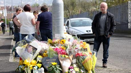 People gather around the floral tributes placed at the site of the killing in the Creggan area of Londonderry in Northern Ireland on Saturday.