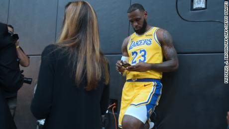 LA Lakers' LeBron James checks his cellphone ahead of a press conference