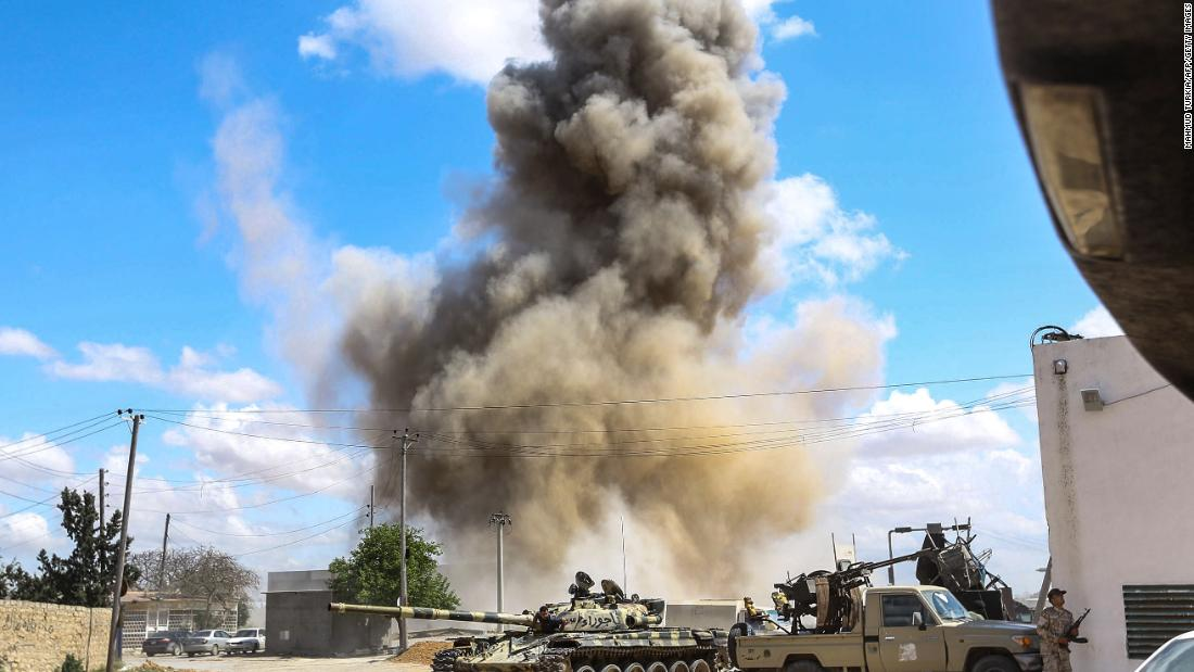 Smoke rises from an airstrike behind a tank and improvised fighting truck belonging to forces loyal to Libya's Government of National Accord, during clashes in Wadi Rabie, south of Tripoli, on April 12.