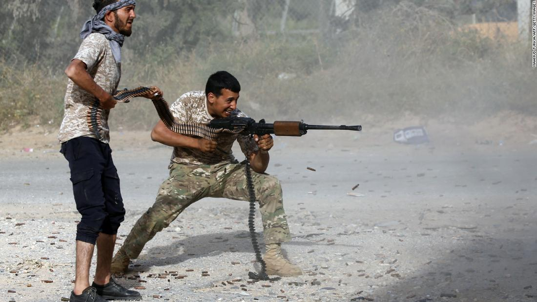 A Libyan fighter loyal to the Government of National Accord fires as a fellow fighter holds a bullet chain during clashes with Haftar's troops south of Ain Zara on April 20.