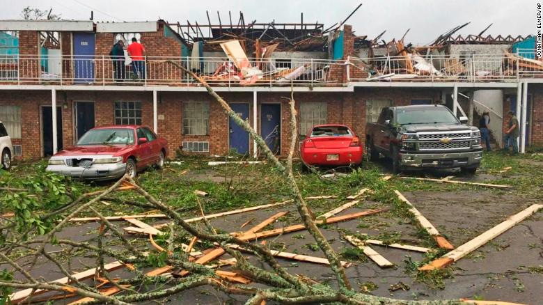 Mọi người khảo sát thiệt hại tại một nhà nghỉ đã bị một cơn lốc xoáy vào thứ năm ở Ruston, Louisiana.