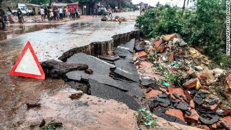 Residents stand next to a road partially destroyed by floods after heavy downpours in the Mozambican city of Pemba Sunday.