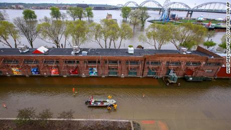 Firefighters walk a rescue boat down West River Drive along the freight house in Davenport on Tuesday April 30