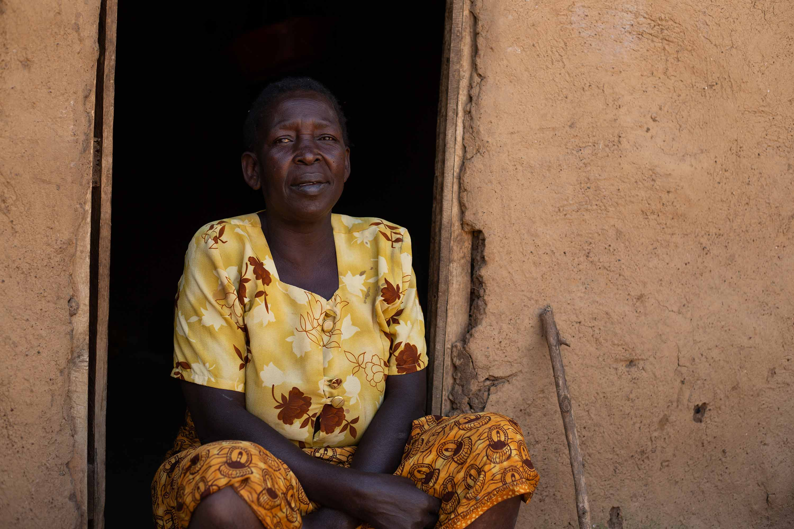 Christina Wambura, 64, sitting in the doorway of her home.