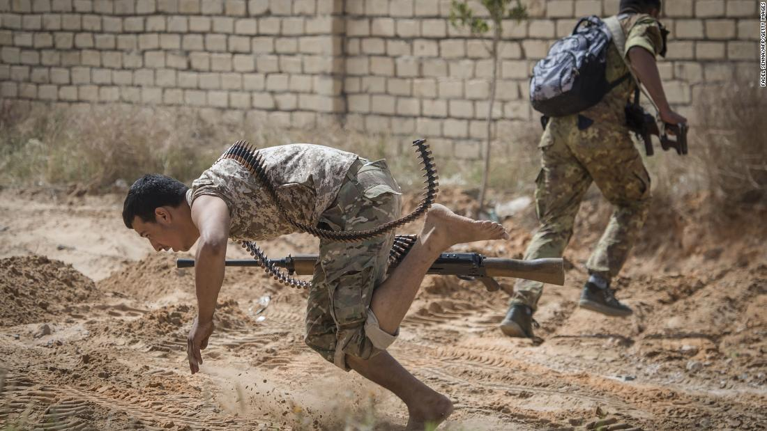 Fighters loyal to the Government of National Accord run for cover during clashes with forces loyal to Field Marshal Khalifa Haftar south of the Tripoli suburb of Ain Zara on April 25.