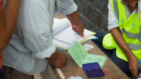 Aid recipients mark a thumbprint to confirm they have received supplies.