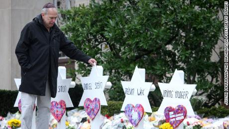 A man walks past memorials in front of the Tree of Life Synagogue after 11 people were shot and killed there in 2018.