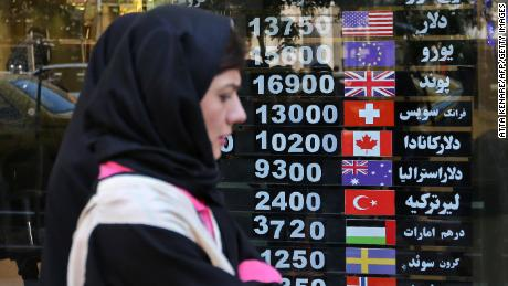 Une Iranienne passe devant un bureau de change dans la capitale, à Téhéran, où les Iraniens sont durement frappés par les sanctions économiques sévères imposées par les États-Unis.
