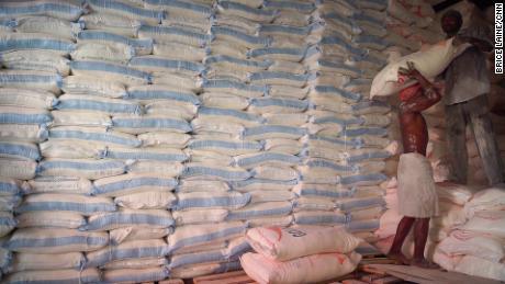 Men stack sacks of flour at a warehouse for WFP supplies in Hodeidah.