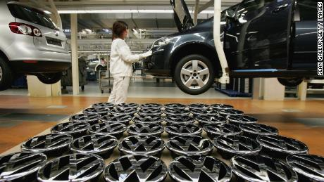 A worker stands by Volkswagen hood ornaments at the Golf production line at the Volkswagen factory in Wolfsburg, Germany.