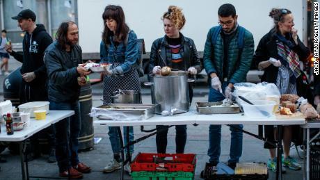 Un repas chaud gratuit est servi par des bénévoles de Refugee Community Kitchen aux personnes se trouvant à l'extérieur de la station de métro Camden Town le 17 avril à Londres, en Angleterre.