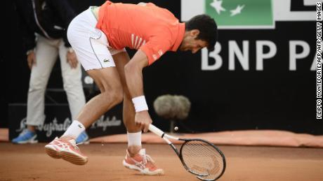 Novak Djokovic smashes his racquet after being broken.