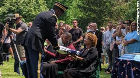 Funeral director, Lynay Straughn, recieving the flag on behalf of Perkins' family.