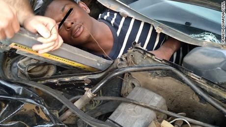Un homme se glissa dans un compartiment construit derrière un tableau de bord de voiture.