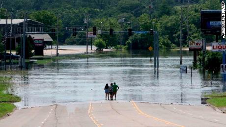 Les gens se tiennent au milieu de la rue et regardent le Massard Creek inondé dans l'Arkansas.
