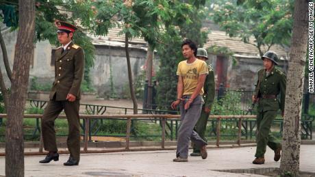 Un homme menotté est conduit par des soldats chinois dans une rue de Pékin le 14 juin 1989, alors que la police et les soldats continuent de rechercher des personnes impliquées dans des manifestations en faveur de la démocratie.
