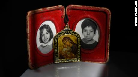 Childhood photographs of siblings Carla and Carlos Jr. Their mother carries these photographs and a necklace of the Virgin Mary everywhere she goes.