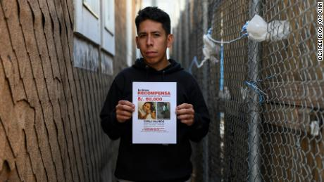 Carlos Jr. holds a reward flyer in the Brooklyn alleyway where he last saw his missing sister in person.