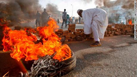 Les manifestants soudanais ferment la rue 60 avec des pneus en feu et des pavés alors que les forces militaires tentaient de disperser le sit-in devant le siège de l'armée de Khartoum le 3 juin 2019.