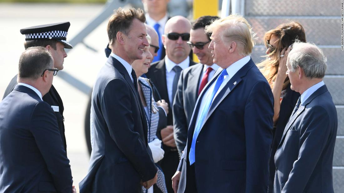 Trump is greeted by UK Foreign Secretary Jeremy Hunt after arriving at the airport.