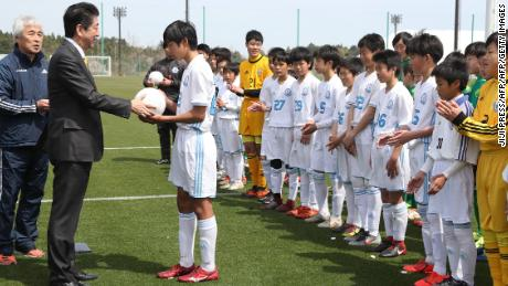 Le Premier ministre Shinzo Abe présente un ballon à un club de football local plus tôt cette année lorsque le J-Village a été relogé.