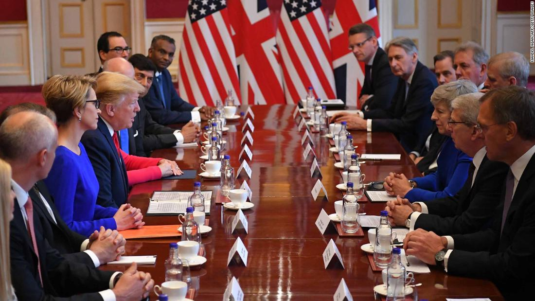 Trump speaks opposite May at a business roundtable discussion in London.