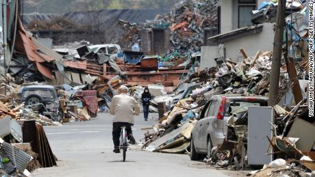 A resident cycles through the rubble of Kamaishi two months after the tsunami.