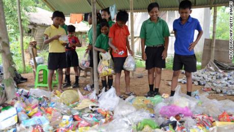 Des étudiants indiens recueillent des sacs en plastique avant de les verser à l'école Akshar Forum de Pamohi, dans la banlieue de Guwahati, le 20 mai 2019.