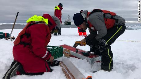 Mesurer l'épaisseur et la densité d'un noyau de glace récemment extrait.