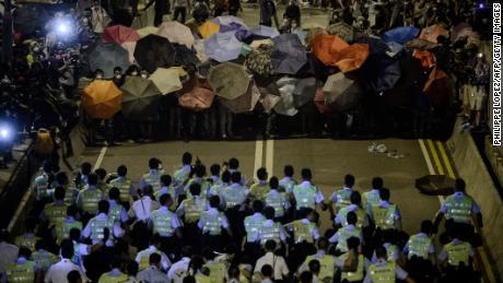 Police forces march toward pro-democracy protesters during a standoff outside the central government offices in Hong Kong on October 14, 2014.