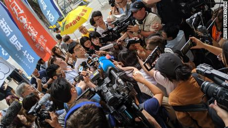 Hong Kong protest icon Joshua Wong is greeted by a scrum of media as he leaves prison on June 17, 2019.