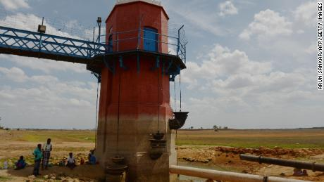 Men sit in the shade of a measuring tower at the dried-out Puzhal reservoir on the outskirts of Chennai on Friday.